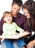 Madre, fathher y pequeño libro de lectura de la hija Foto de archivo libre de regalías