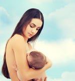 Madre felice che alimenta il suo bambino adorabile Fotografia Stock