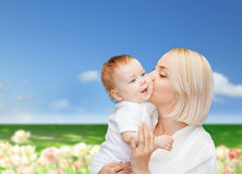 Madre felice che bacia bambino sorridente Fotografia Stock
