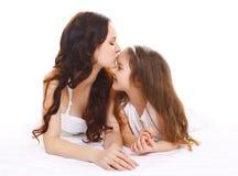 Madre felice che bacia la figlia del piccolo bambino su bianco fotografia stock