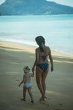Madre felice che cammina con la piccola figlia lungo la spiaggia Fotografia Stock Libera da Diritti