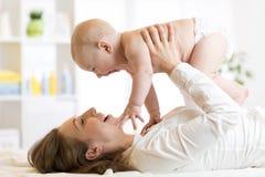Madre felice che gioca con il neonato fotografia stock libera da diritti