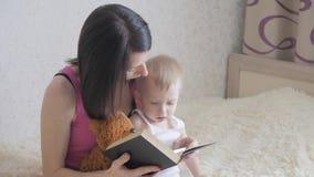Madre felice che legge un libro al ragazzo del bambino all'interno Momento dolce con il libro di lettura della madre al bambino stock footage