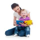 Madre felice che legge un libro alla neonata Fotografia Stock