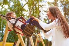 Madre felice che spinge figlio di risata Immagine Stock