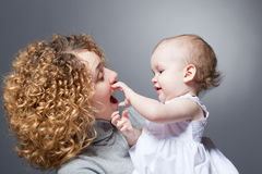 Madre felice che tiene bambino sorridente sveglio immagine stock