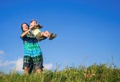 Madre felice con divertimento del figlio sulla passeggiata in alta erba contro cielo blu Immagini Stock Libere da Diritti