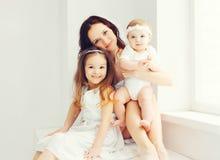 Madre felice con due i suoi bambini delle figlie a casa fotografia stock libera da diritti