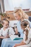 madre felice con gli anni 50 adorabili del libro di lettura dei bambini insieme a casa fotografia stock