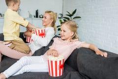 madre felice con i bambini svegli che mangiano insieme popcorn fotografia stock libera da diritti