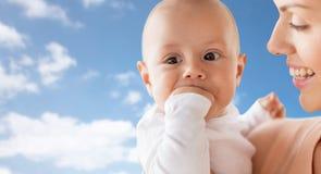 Madre felice con il bambino che succhia le dita sopra il cielo Immagini Stock Libere da Diritti
