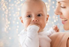 Madre felice con il bambino che succhia le dita sopra le luci Fotografia Stock Libera da Diritti