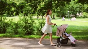 Madre felice con il bambino in passeggiatore che cammina al parco video d archivio