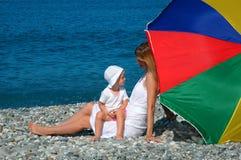 Madre felice con il bambino sotto l'ombrello sulla spiaggia fotografia stock libera da diritti