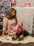 Madre felice con il figlio neonato, sedentesi su un pavimento vicino ad un albero di Natale Aspettando una festa fotografia stock