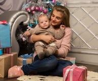 Madre felice con il figlio neonato, sedentesi su un pavimento vicino ad un albero di Natale Aspettando una festa fotografia stock libera da diritti