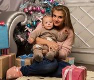 Madre felice con il figlio neonato, sedentesi su un pavimento vicino ad un albero di Natale Aspettando una festa immagine stock libera da diritti