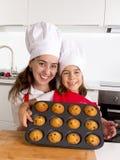 Madre felice con il grembiule d'uso della figlia e cappello del cuoco che presenta muffin stabilito cocendo insieme a casa cucina Immagine Stock