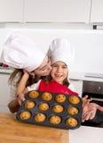 Madre felice con il grembiule d'uso della figlia e cappello del cuoco che presenta muffin stabilito cocendo insieme a casa cucina Fotografia Stock