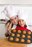 Madre felice con il grembiule d'uso della figlia e cappello del cuoco che presenta muffin stabilito cocendo insieme a casa cucina Fotografia Stock Libera da Diritti