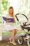 Madre felice con il libro ed il passeggiatore in parco Immagini Stock Libere da Diritti