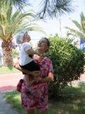 Madre felice con il neonato sveglio che ha vacanza tropicale sulle Maldive Bambino che gioca fra le palme Fotografie Stock Libere da Diritti