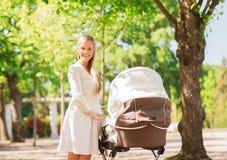 Madre felice con il passeggiatore in parco Fotografia Stock Libera da Diritti