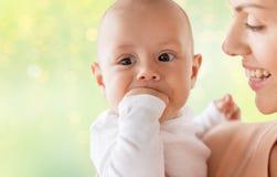 Madre felice con il piccolo neonato che succhia le dita Fotografia Stock