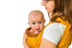 Madre felice con il suo bambino in un'imbracatura - isolata su bianco Immagini Stock