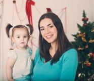 Madre felice con la figlia vicino all'albero di Natale Immagini Stock Libere da Diritti