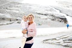 Madre felice con la piccola neonata che viaggia in zaino Escursione dell'avventura con il bambino in montagne immagini stock