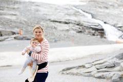 Madre felice con la piccola neonata che viaggia in zaino Escursione dell'avventura con il bambino in montagne immagine stock libera da diritti