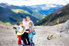 Madre felice con la piccola neonata e due i ragazzi dei bambini che viaggiano in zaino fotografia stock