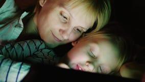 Madre felice con la sua figlia Gioco insieme parallelamente sulla compressa, bugia faccia a faccia a letto archivi video