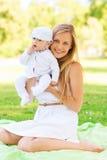 Madre felice con poco fare da baby-sitter sulla coperta Immagini Stock Libere da Diritti