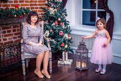 Madre felice con sua figlia che gioca vicino all'albero di Natale Immagini Stock Libere da Diritti