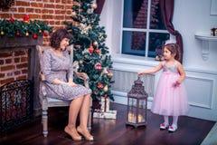 Madre felice con sua figlia che gioca vicino all'albero di Natale Fotografia Stock