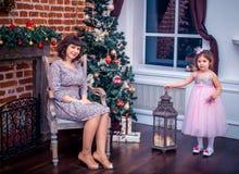 Madre felice con sua figlia che gioca vicino all'albero di Natale Fotografia Stock Libera da Diritti