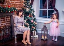 Madre felice con sua figlia che gioca vicino all'albero di Natale Fotografie Stock Libere da Diritti