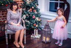 Madre felice con sua figlia che gioca vicino all'albero di Natale Immagine Stock Libera da Diritti