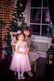 Madre felice con sua figlia dal camino Immagine Stock Libera da Diritti