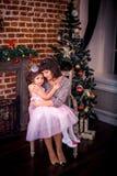 Madre felice con sua figlia dal camino Fotografia Stock