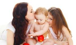 Madre felice della famiglia con il piccolo bambino della figlia che bacia bambino Fotografia Stock Libera da Diritti