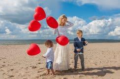 Madre felice della famiglia e due ragazzi con i palloni rossi del cuore Fotografia Stock Libera da Diritti