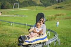 Madre felice della famiglia e figlia del bambino piccola nel toboggan di estate Immagine Stock
