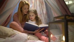 Madre felice della famiglia e sua piccola la figlia che leggono un libro in una tenda a casa stock footage