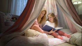 Madre felice della famiglia e sua piccola la figlia che leggono un libro in una tenda a casa archivi video
