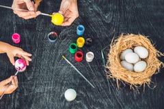 Madre felice di pasqua A, padre ed il loro figlio dipingenti le uova di Pasqua Famiglia felice che prepara per Pasqua Fotografia Stock Libera da Diritti