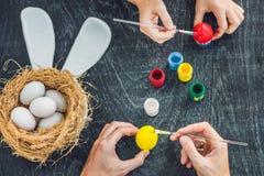 Madre felice di pasqua A, padre ed il loro figlio dipingenti le uova di Pasqua Famiglia felice che prepara per Pasqua Immagini Stock