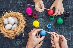 Madre felice di pasqua A, padre ed il loro figlio dipingenti le uova di Pasqua Famiglia felice che prepara per Pasqua Fotografia Stock